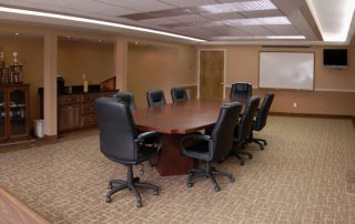 Peach colored conference room with table & chairs