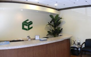white office with wood front desk & green cube on wall